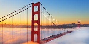 Golden Gate Bridge above fog at sunrise